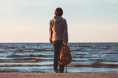 jeune-femme-de-touristes-avec-le-sac-à-dos-regardant-à-la-mer-58769513