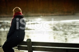 stock-photo-15264902-woman-sits-alone-on-a-bench-across-the-river