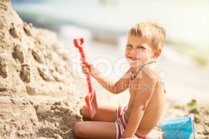 stock-photo-55376046-little-boy-building-a-sandcastle