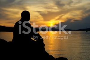 stock-photo-9914372-silhouette-of-a-man-at-sunset-looking-at-the-water