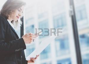 54418828-femme-pbusiness-portant-le-costume-regardant-smartphone-et-la-tenue-des-documents-dans-les-mains-esp