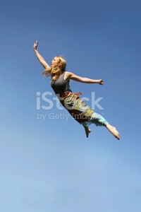 A young woman is jumping up as if flying through the air in front of a blue sky background.