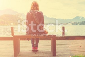stock-photo-79935625-girl-sitting-on-a-wooden-pier-near-water-