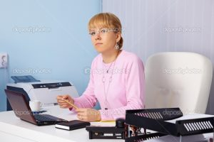 The young serious woman - the chief sits in an office