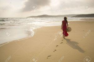 14786845-jeune-femme-marcher-sur-une-plage-d-serte-sauvage-vers-des-faisceaux-de-lumi-re-c-lestes-qui-tombent-banque-dimages
