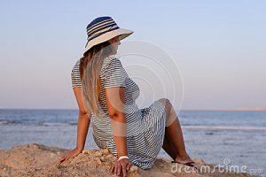 femme-romantique-apprciant-la-brise-au-bord-de-la-mer-58540887
